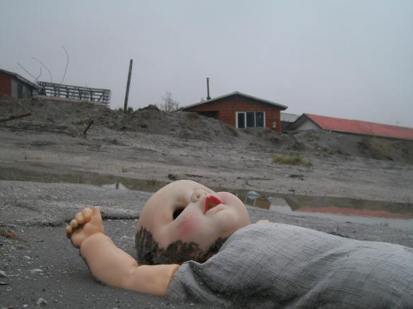 Child's doll abandoned in the ash by lopsided buildings.