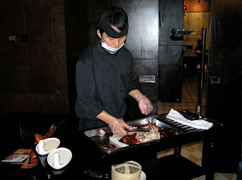 Chef prepares to serve Peking Duck at 1949 The Hidden City