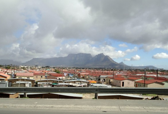 Table Mountain looms in the background of a Cape Town township.