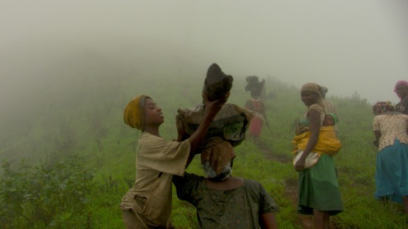 Tree trunks (for firewood) are carried up the steep mountainside, atop the women's heads